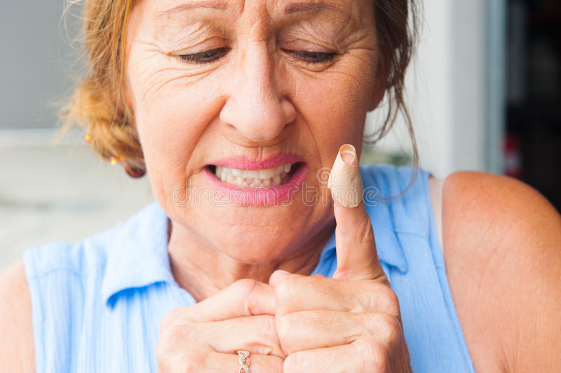 Senior Woman band aid blood finger wound. Portrait woman with stressed facial expression, in pain, hurt and suffering, close up of band aid on injured, cut royalty free stock photo