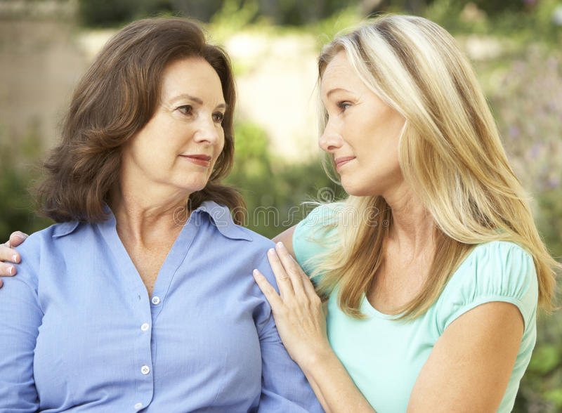 Senior Woman Being Consoled By Adult Daughter stock photos