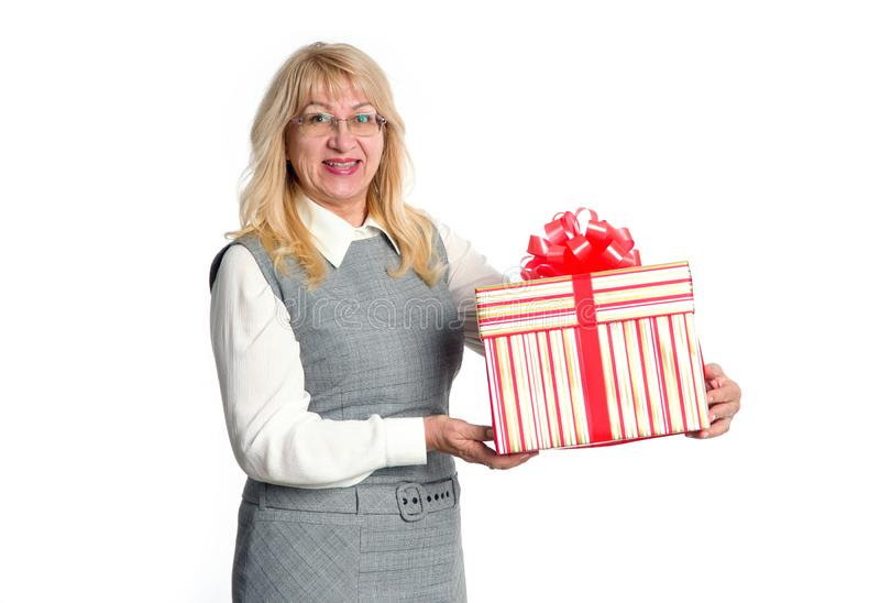 Mature woman with big gift box. Senior woman with big gift box in hand on a light background royalty free stock images