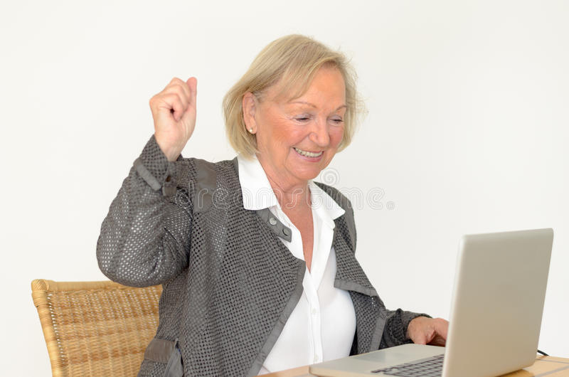 Senior woman in business look in front of a silver laptop. Active blond senior woman with formal clothes and friendly smile showing fist up while sitting at desk royalty free stock photo