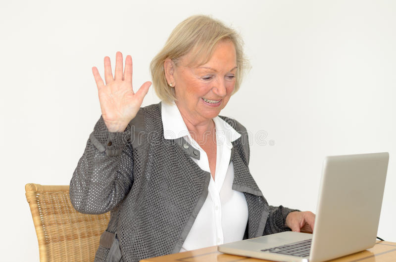 Senior woman in business look in front of a silver laptop. Active blond senior woman with formal clothes and friendly smile showing hand up while sitting at desk stock photos