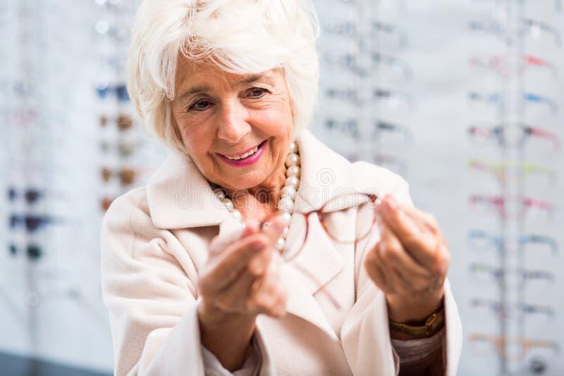 Senior woman buying new eyeglasses royalty free stock photos