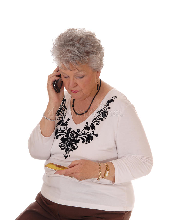 Senior woman buying over phone. A mature senior woman buying with a credit card and her cell phone, isolated for white background royalty free stock images