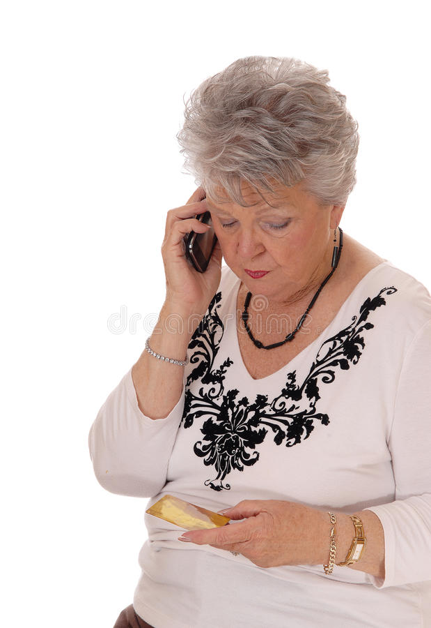 Senior woman buying over phone. A mature senior woman buying with a credit card over her cell phone, isolated for white background stock photos