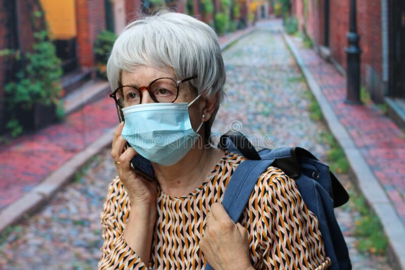 Senior woman calling by phone during pandemic stock photo