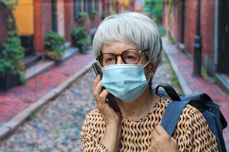 Senior woman calling by phone during pandemic stock images