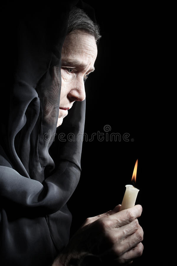 Senior woman with candle dark profile. Sad old woman in sadness portrait stock photos