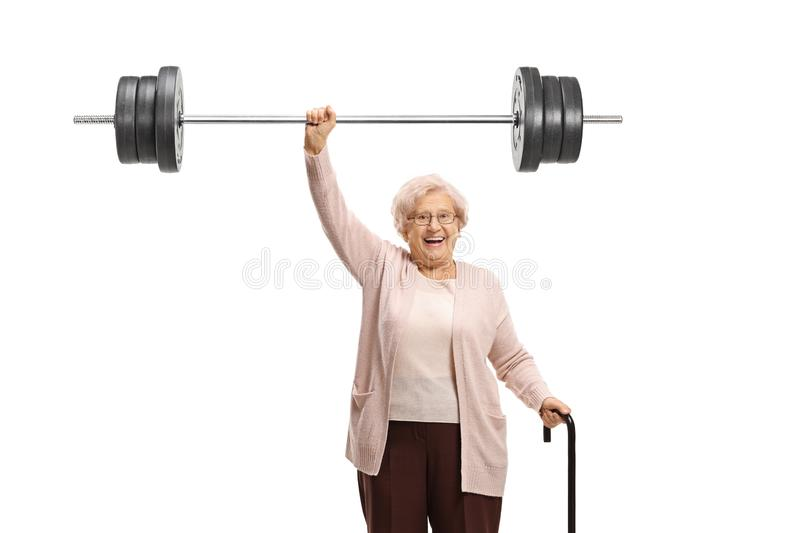 Senior woman with a cane liftiing a barbell. Isolated on white background stock image