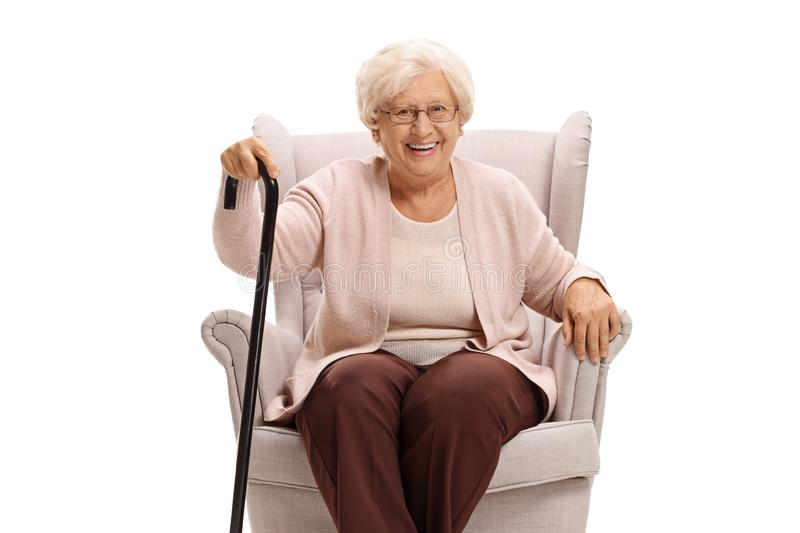 Senior woman with a cane sitting in an armchair. And looking at the camera isolated on white background royalty free stock image