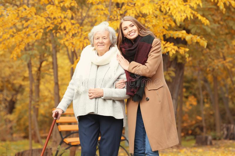 Senior woman with cane and young caregiver. Senior women with cane and young caregiver in park royalty free stock image