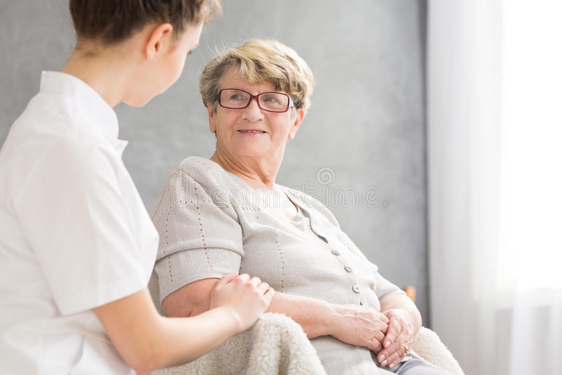 Senior woman and caregiver. Smiling elderly women and professional female caregiver royalty free stock photos