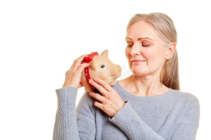 Senior woman carries piggy bank on shoulder royalty free stock images
