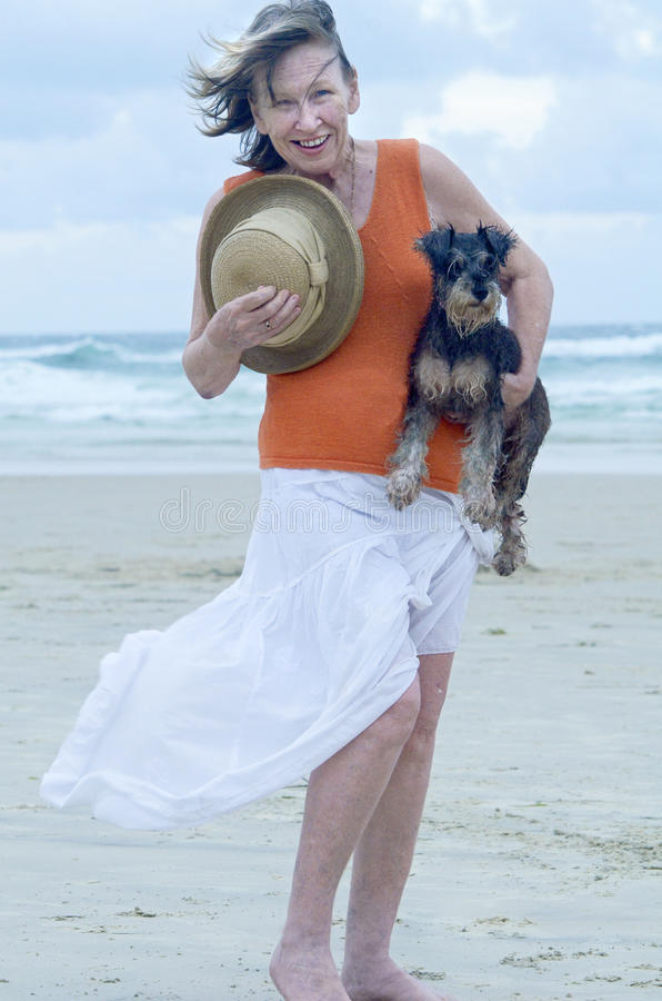 Senior woman carrying pet puppy dog on the beach for day out royalty free stock photography