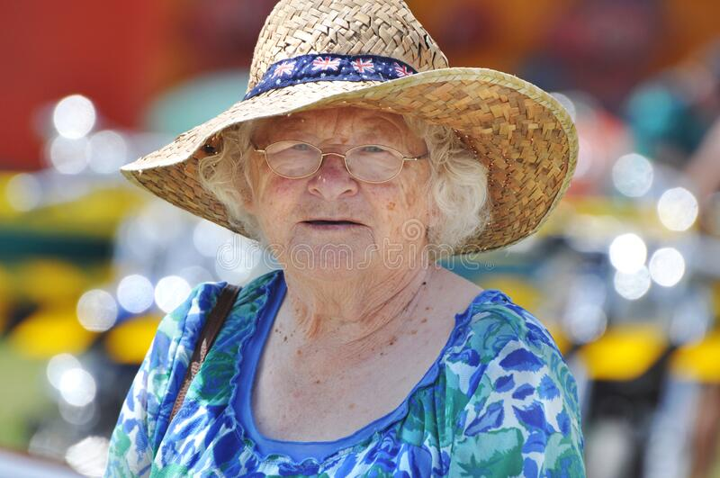 Senior woman celebrating Australia Day in traditional flags hat outdoors. A close-up portrait of an elderly, senior old woman enjoying the celebrations of stock image