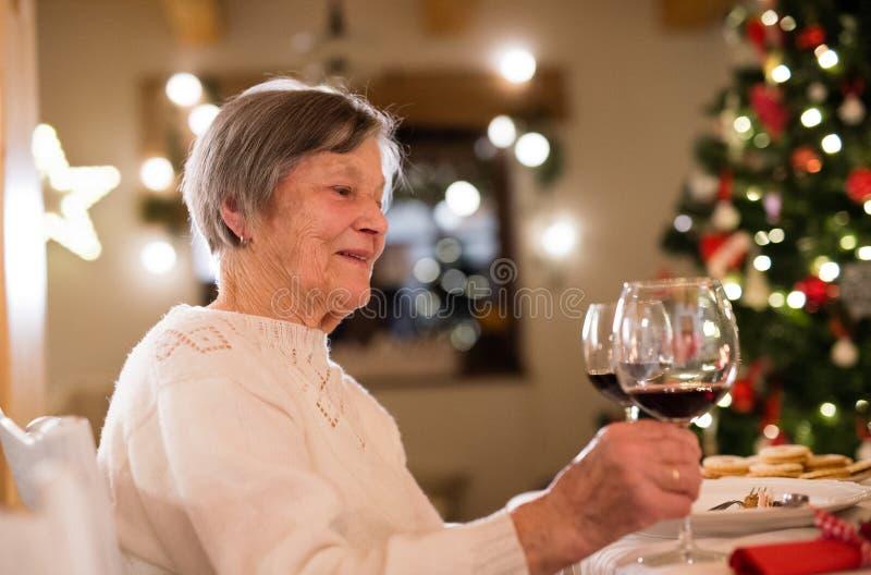 Senior woman celebrating Christmas with her family. Beautiful senior woman celebrating Christmas with her family, holding a glass of red wine stock photos
