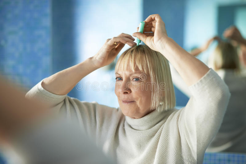 Senior woman checking hairline for hair loss stock images