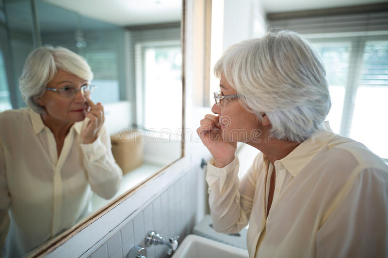 Senior woman checking her skin in mirror stock images