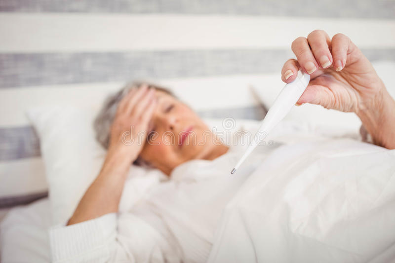 Senior woman checking her temperature stock photography