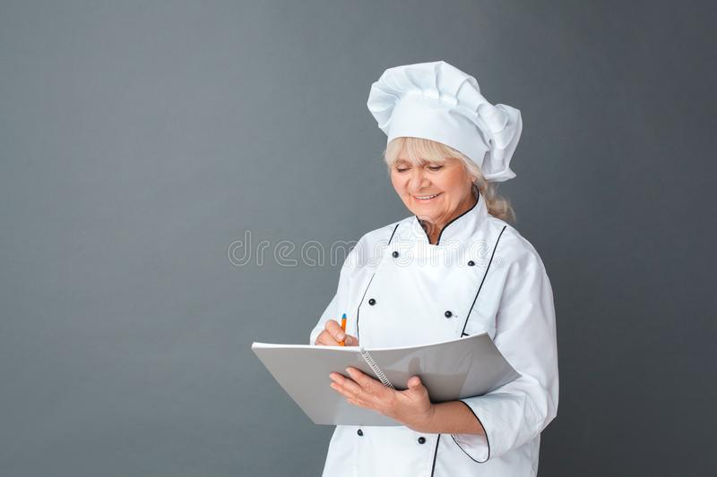 Senior woman chef studio standing isolated on gray writing in journal joyful royalty free stock images