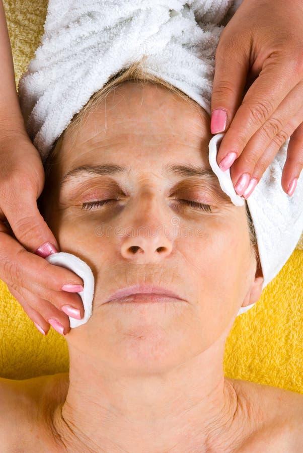Senior woman cleansing face at spa. Senior woman getting a cleansing face at spa retreat stock image