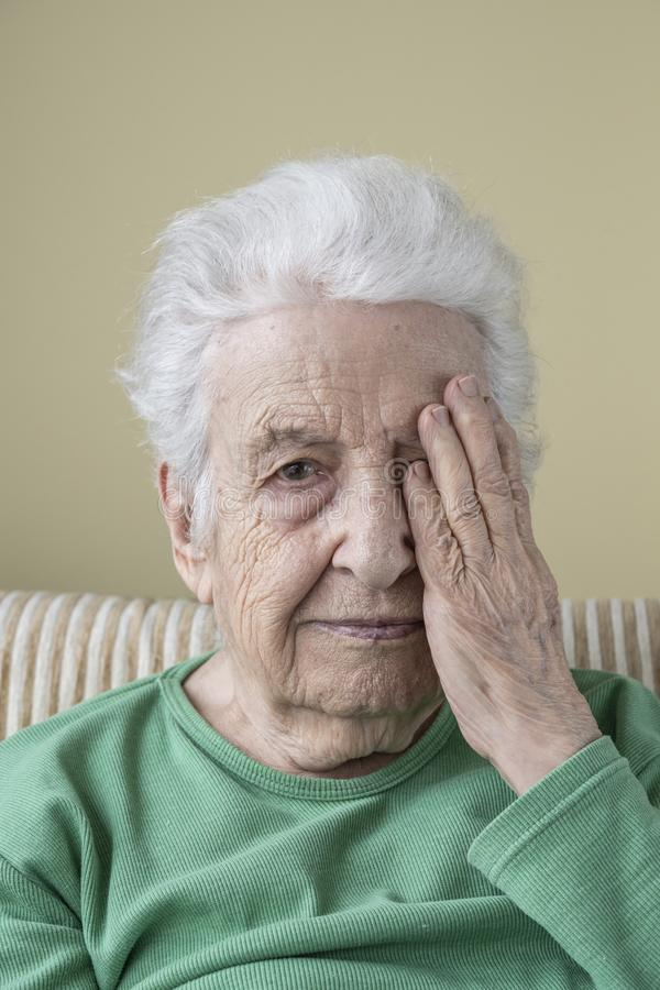 Senior woman closing her one eye with her hand stock photo