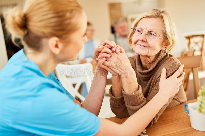 Senior woman is comforted by geriatric nurse. Demented or ill senior women is being comforted by a geriatric nurse in the nursing home stock photos