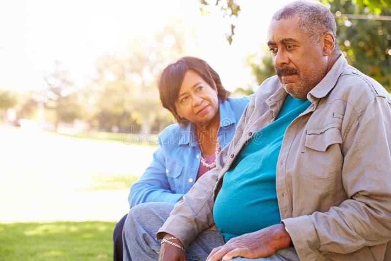 Senior Woman Comforting Unhappy Senior Husband Outdoors royalty free stock image