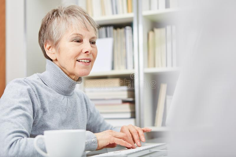 Senior woman with computer stock photography