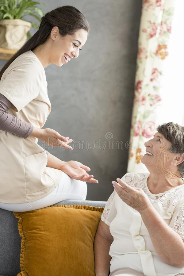 Senior woman conversing with caregiver. Smiling senior women conversing with caregiver in the hospice stock images