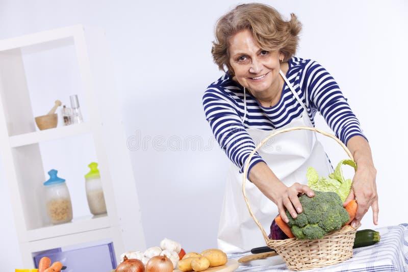 Senior woman cooking royalty free stock photos