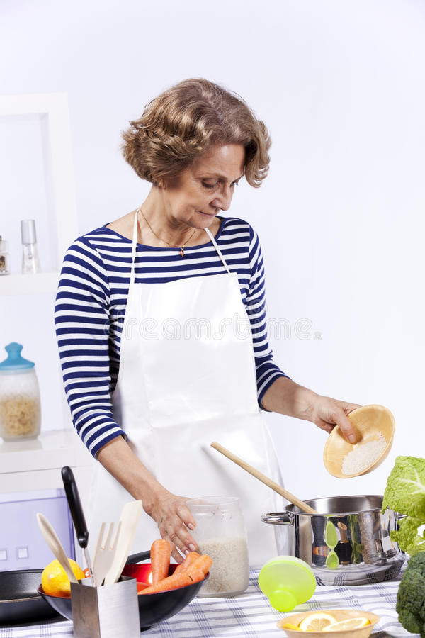 Senior woman cooking royalty free stock images