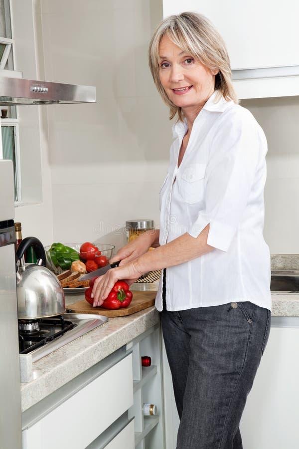 Senior woman cooking food royalty free stock image