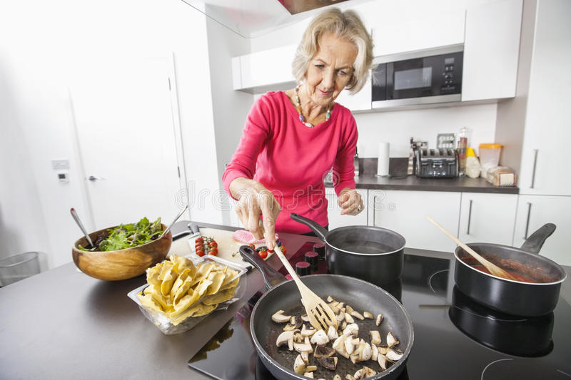 Senior woman cooking food in kitchen stock photo