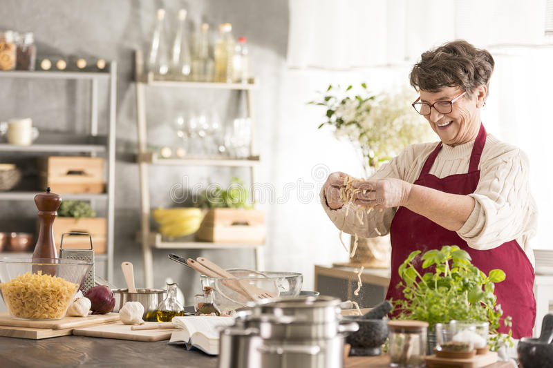 Senior woman cooking. Happy senior woman cooking in her modern kitchen stock photography