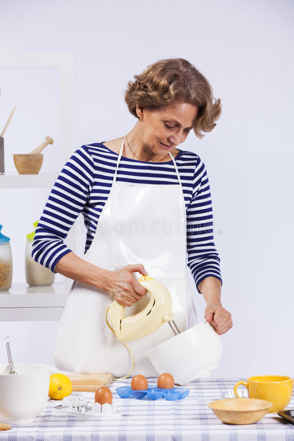 Senior woman cooking royalty free stock photo