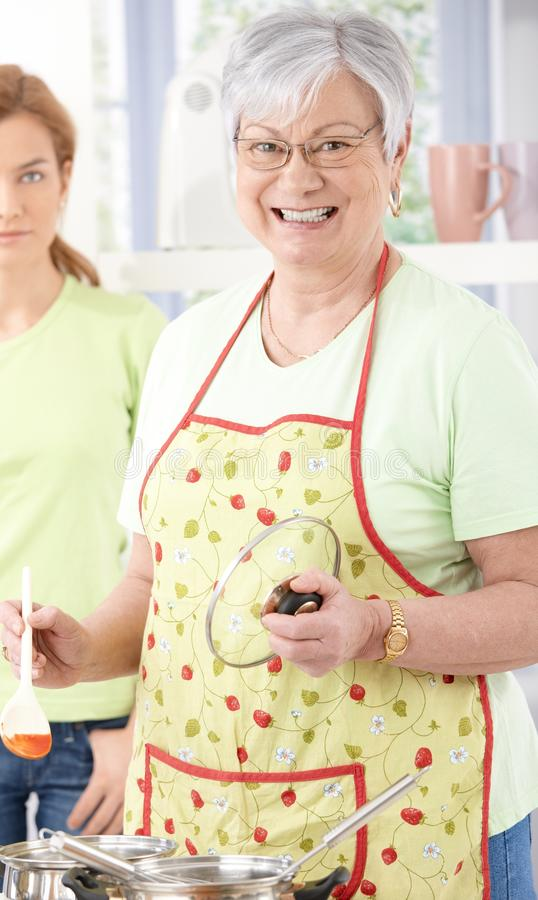 Senior Woman Cooking Smiling Happily Royalty Free Stock Photography