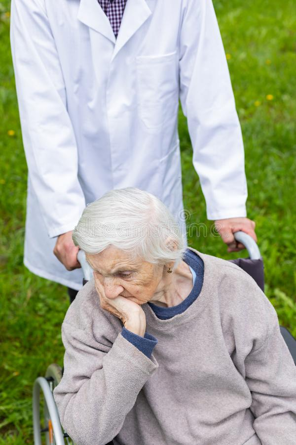 Assisted living. Senior woman with dementia sitting in a wheelchair outdoor, male doctor taking care of her - eldercare royalty free stock images