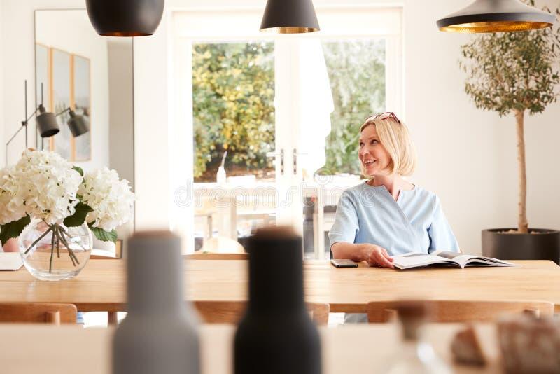 Senior Woman die bij het tijdschrift in het tijdschrift in het huis van de Lezing aan de slag gaat bij de tafel van de vergaderza stock foto's