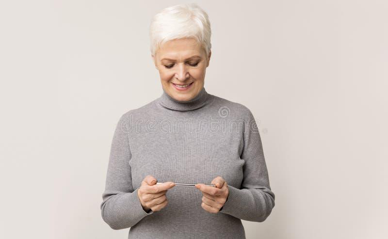Senior woman die videospel speelt op mobiele telefoon en glimlachend stock foto's