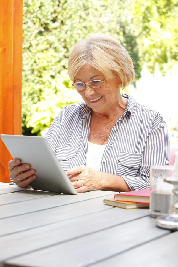 Senior woman with digital tablet royalty free stock photography