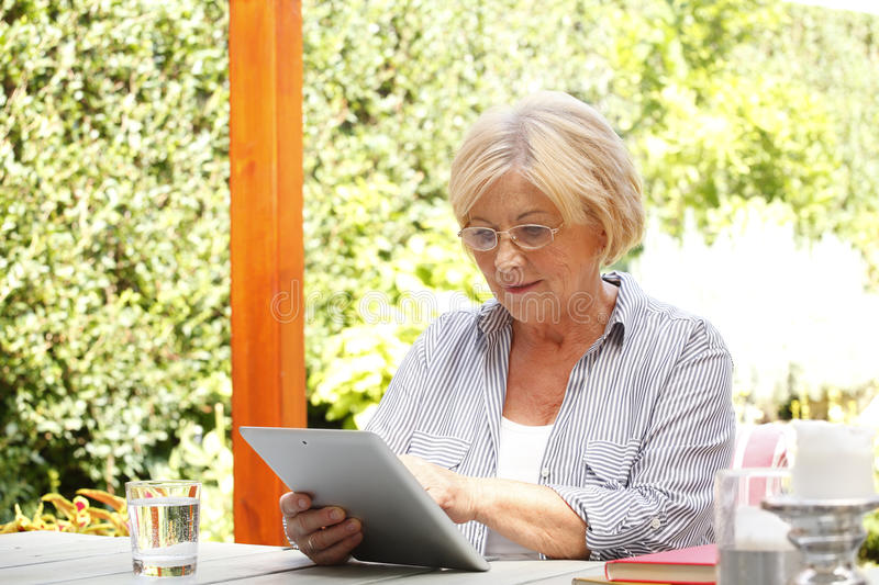 Senior woman with digital tablet stock images
