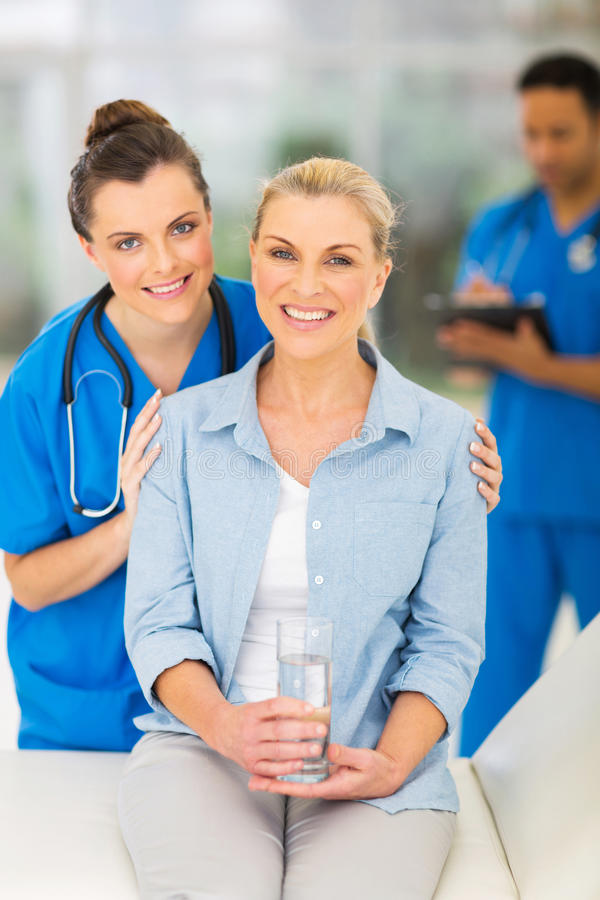 Senior woman doctor. Beautiful senior women in doctor's office with young nurse stock photo