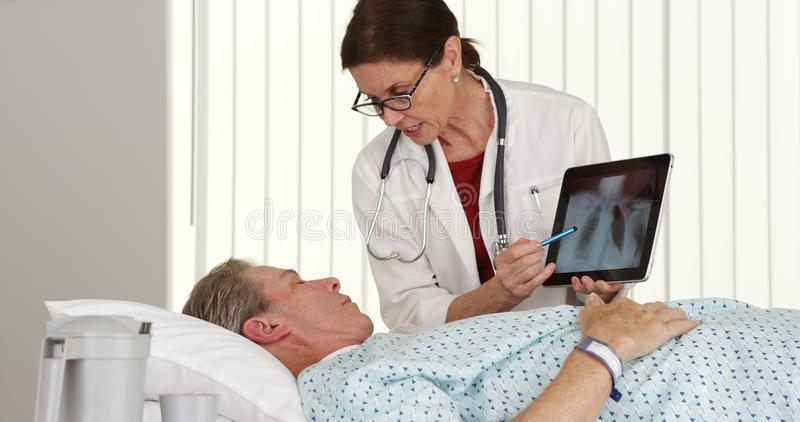 Senior woman doctor talking to elderly patient lying in bed stock image