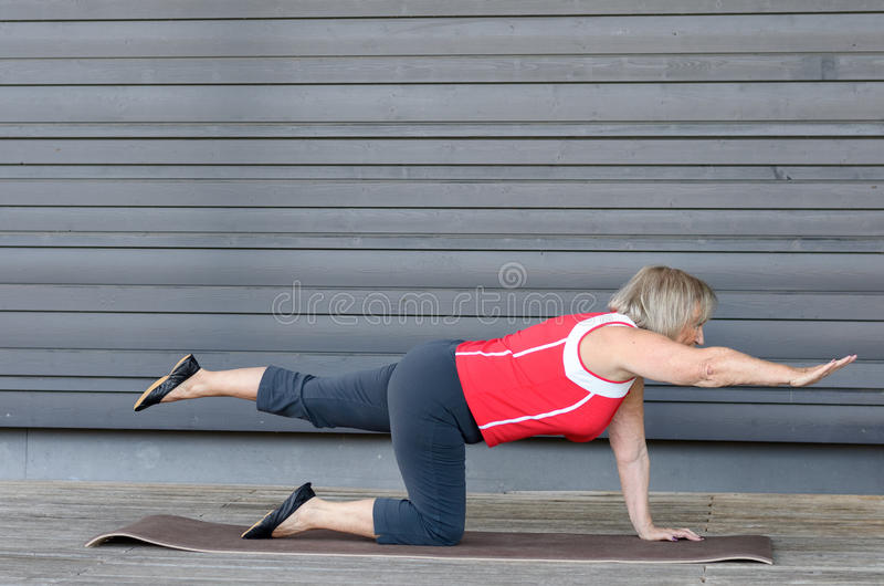 Senior woman doing exercises on a gym mat royalty free stock photos