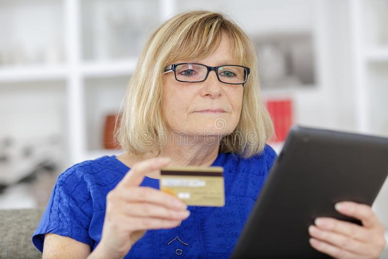 Senior woman doing online shopping stock photo