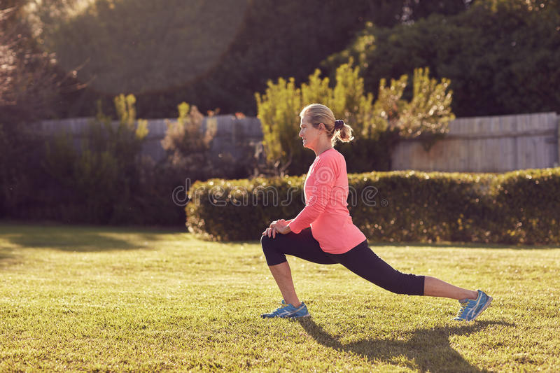 Senior woman doing runner's lunges in morning sunlight stock images