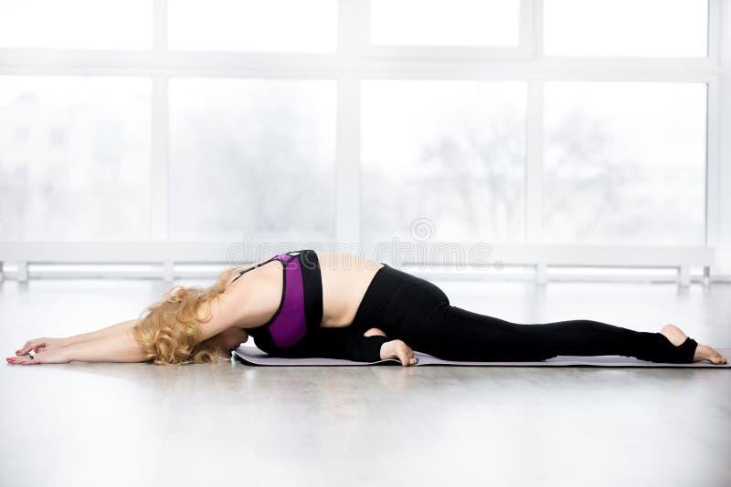 Senior woman doing Sleeping Swan yoga pose royalty free stock photo