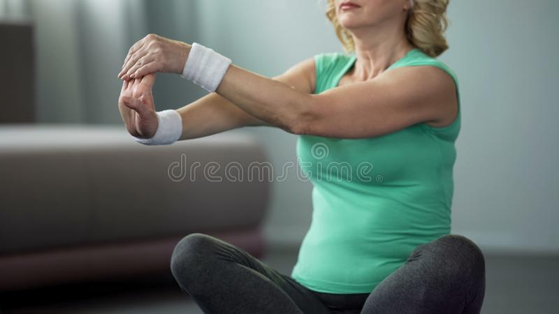 Senior woman doing stretching exercise at home, active lifestyle, health care stock photo