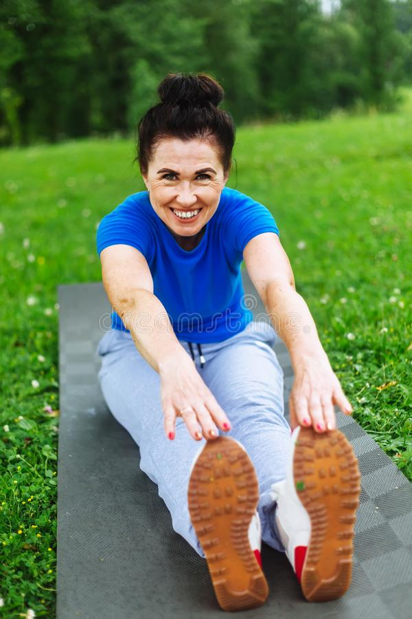 Happy Senior woman doing stretching exercises in park royalty free stock photos