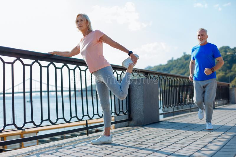 Senior woman doing stretching exercises while man jogging royalty free stock images